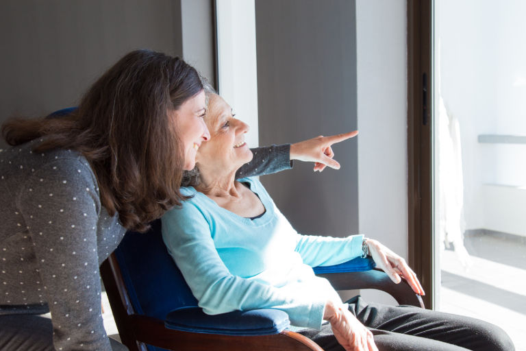 Positive mother and daughter enjoying dramatic view out of window. Young health visitor showing to senior lady funny scene out of window. Family relations concept